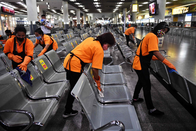 Cleaners disinfect seats in the waiting area at Mo Chit Bus Terminal in Bangkok in January 5, 2021, following a surge in cases of the Covid-19 coronavirus in Thailand. (Photo by Lillian Suwanrumpha/AFP Photo)