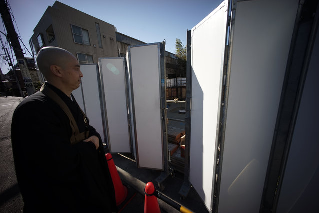 In this January 8, 2015 photo, a monk Kenmyo Muta looks at the condominium construction site next to Sengakuji temple in Tokyo. (Photo by Eugene Hoshiko/AP Photo)