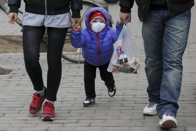 """A child wears a protective mask to shield from extreme smog in central Beijing December 8, 2015 as China's capital issues its first ever """"red alert"""" for pollution. (Photo by Damir Sagolj/Reuters)"""