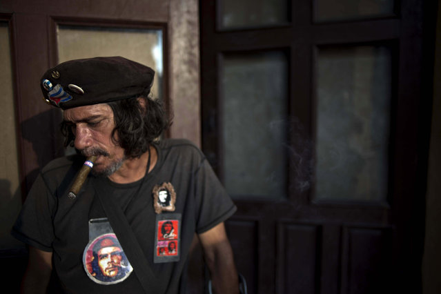 """Jorge Gonzalez, dressed as Cuba's late revolutionary hero Ernesto """"Che"""" Guevara, poses for a photo in the street in Havana, Cuba, Monday, January 19, 2015. Gonzalez, who studied metallurgy in college, takes advantage of his resemblance to Che by spending time downtown where tourists tip him for posing for photos. (Photo by Ramon Espinosa/AP Photo)"""