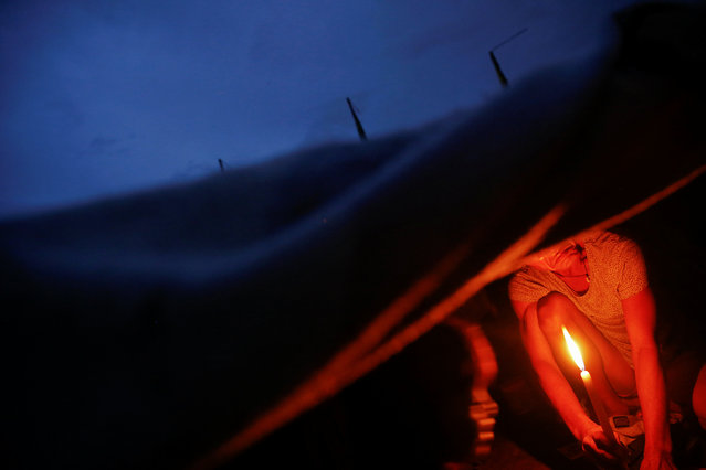 A man lights a candle in his family's shack in an area where, according to local residents, several people have been killed in police operations since the beginning of country's war on drugs, in Manila, Philippines November 2, 2016. (Photo by Damir Sagolj/Reuters)