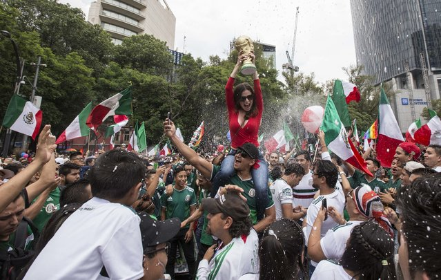 In this Saturday, June 23, 2018 photo, soccer fans and gay pride parade revelers converge on Reforma Avenue in Mexico City. Soccer fans were celebrating Mexico's victory over Korea at a World Cup soccer match in Russia as they met the massive gay pride parade marching toward downtown. (Photo by Christian Palma/AP Photo)