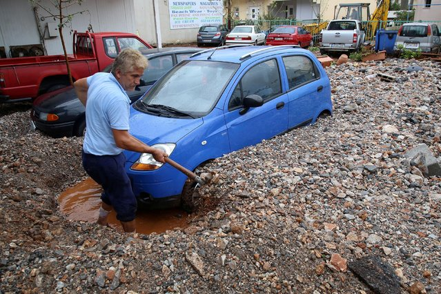 A local shovels mud blocking a car, following heavy rainfall in Malia on the island of Crete, Greece, November 10, 2020. (Photo by Stefanos Rapanis/Reuters)
