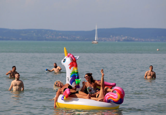 Festival goers lie on an air mattress in Lake Balaton during the Balaton Sound music festival in Zamardi, Hungary, July 5, 2018. (Photo by Bernadett Szabo/Reuters)
