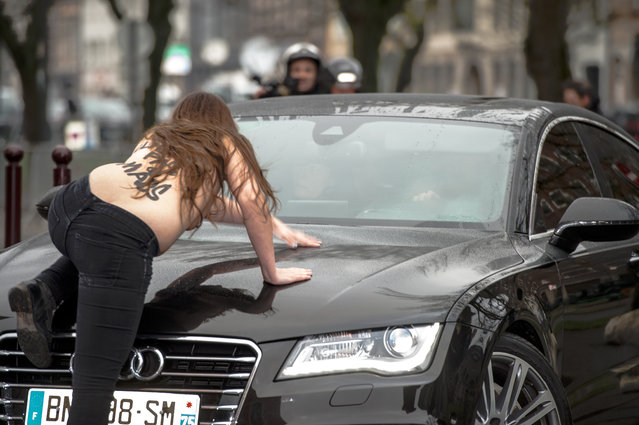 """A topless Femen activist jumps on the car carrying former IMF chief Dominique Strauss-Kahn (not seen) as he arrives for his trial in Lille, northern France, on February 10, 2015. Three topless women from the protest group Femen jumped on the car of Dominique Strauss-Kahn as the former IMF chief arrived to testify at his trial for """"aggravated pimping"""". With slogans scrawled on their half-naked bodies and hurling insults at the car, the three protesters were quickly rounded up by police as the car entered an underground parking area. (Photo by Denis Charlet/AFP Photo)"""