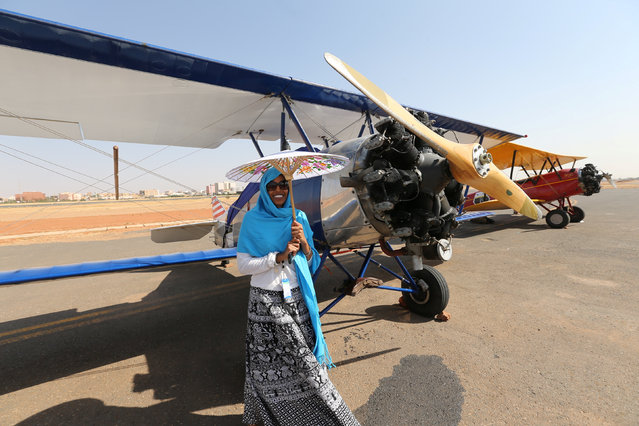A woman poses next to a biplane after 18 biplanes landed at Khartoum Airport in Sudan during a tour across Africa, November 20, 2016. (Photo by Mohamed Nureldin Abdallah/Reuters)