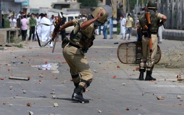 A Kashmiri paramilitary trooper throws a stone during a clash between protestors and Indian police officials in Srinagar on August 9, 2013. At least 30 people including 20 police were injured during clashes that broke out after Eid prayers in Srinagar, Indian Kashmir's main city, a police official and witnesses said. Indian police and paramilitary forces fired tear smoke shells and pallet guns at hundreds of protestors throwing rocks at them near the main prayer ground Eidgah in the old town area of the summer capital of the Himalayan state. (Photo by Tauseef Mustafa/AFP Photo)