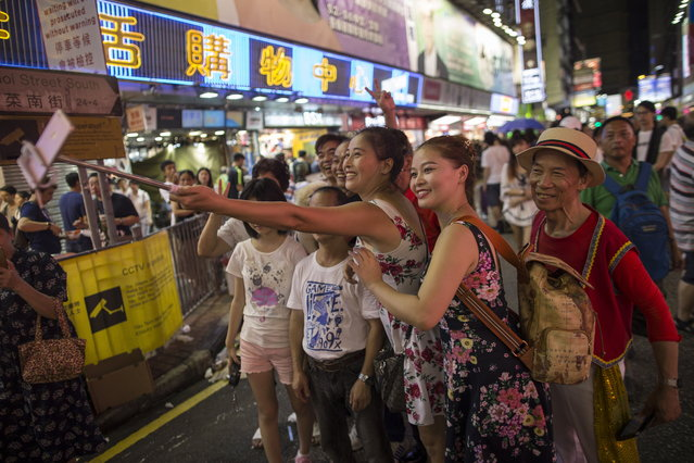 Members of the public taking selfies with buskers in Sai Yeung Choi Street South in Mongkok district, Hong Kong, China, 28 July 2018. (Photo by Jerome Favre/EPA/EFE)