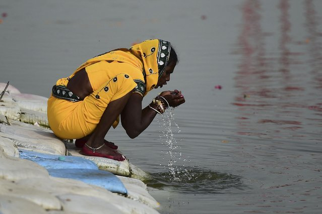 A Hindu devotee drinks water from the Ganges River at the Sangam area, the confluence of rivers Ganges, Yamuna, and the mythical Saraswati, in Allahabad on March 16, 2021. (Photo by Sanjay Kanojia/AFP Photo)