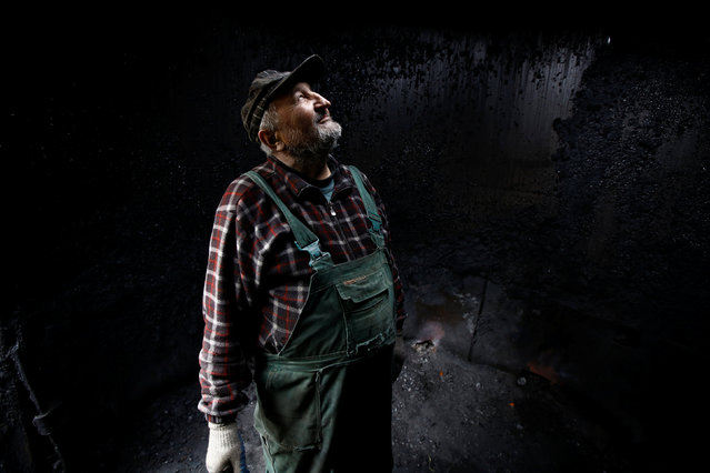 Charcoal burner Zygmunt Furdygiel looks up inside an empty charcoal furnace before loading it with wood at a charcoal making site in the forest of Bieszczady Mountains, near the village of Baligrod, Poland October 27, 2016. (Photo by Kacper Pempel/Reuters)