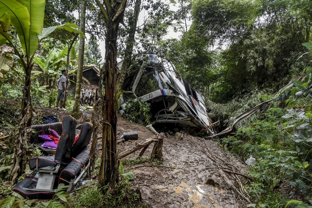 Residents inspect the wreckage of a bus that plunged into a ravine in Sumedang West Java, Thursday, March 11, 2021. The tourist bus carrying a group of Islamic junior high school students, teachers and parents plunged into the 20-meter (65-foot) -deep ravine after its brakes apparently malfunctioned, killing a number of people, police and rescuers said. (Photo by Ahmad Fauzan/AP Photo)