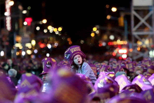 A child is lifted above the crowd during New Year celebrations in Times Square in the Manhattan borough of New York December 31, 2015. (Photo by Andrew Kelly/Reuters)
