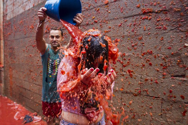"""A young man throws a bucket of squashed tomatoes to a friend during the traditional tomato fight """"Tomatina"""" during the fiestas in Bunol, Spain, 28 August 2013. This year's Tomatina is the first pay festival after Bunol's City Hall sold 15,000 tickets to take part in the tomato throwing. A total of 20,000 people, including 5,000 residents, will throw over 130,000 kg tomatoes. Local authorities decided to sell tickets this year to avoid the overcrowding in previous years in which over 50,000 people took part in the event. (Photo by Biel Alino/EPA)"""
