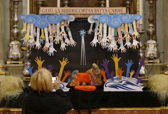 A tourist takes a picture of a Christmas Nativity crib with the traditional figures of Mary, Joseph and baby Jesus in a manger positioned on a life jacket at St Catherine's Church in Valletta, Malta, January 2, 2016. The crib was created in solidarity with migrants, by Italian children living in Malta, who decorated hands reaching out from above to grasp hands symbolizing migrants in the sea, according to their parish priest Father Gino Gauci. (Photo by Darrin Zammit Lupi/Reuters)