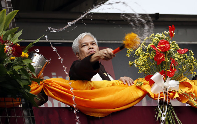 A priest sprinkles holy water on devotees and their religious statues two days before the annual procession of the Black Nazarene in Manila, Philippines January 7, 2016. (Photo by Erik De Castro/Reuters)