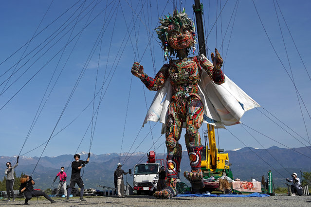 Handlers control the giant puppet MOCCO during a special training session in Takamori, Nagano prefecture, Friday, April 23, 2021. Tokyo 2020 organizers created about 10 meter-tall puppet to symbolize the spirit of the people from the regions affected by the 2011 earthquake and tsunami. The puppet will travel from Tohoku to Tokyo in May to be in place for the games scheduled to open in July. (Photo by Koji Ueda/AP Photo)