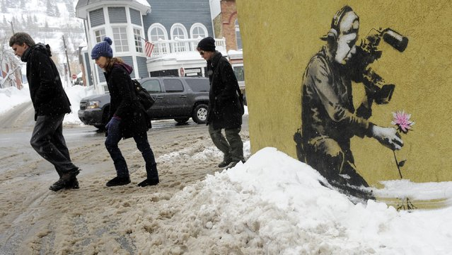 In this January 22, 2010 file photo, festivalgoers walk up Main Street past a design by graffiti artist Banksy during the Sundance Film Festival in Park City, Utah. The 2016 Sundance film festival runs from January 21-31. (Photo by Chris Pizzello/AP Photo)