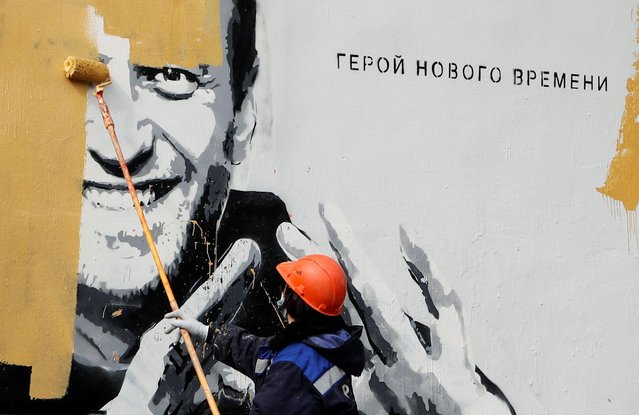 """A worker paints over a graffiti depicting jailed Russian opposition politician Alexei Navalny in Saint Petersburg, Russia on April 28, 2021. The graffiti reads: """"The hero of the new age"""". (Photo by Anton Vaganov/Reuters)"""