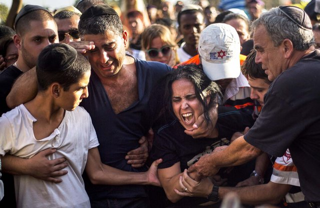 Smadar, mother of Israeli soldier, Staff Sergeant Gabriel Koby, mourns during his funeral at the military cemetery in Haifa, Israel, on September 23, 2013. Koby, 20, was shot and killed by an unknown gunmen in the biblical city of Hebron in the West Bank on Sunday, and troops are searching for the shooter, the military said. It was the second soldier killed since the weekend when a Palestinian killed an Israeli soldier with the intention of trading the body for his brother who is jailed for shooting attacks. (Photo by Ariel Schalit/Associated Press)