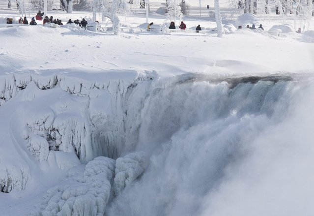 Niagara Falls State Park visitors look over masses of ice formed around the American Falls, photographed from across the Niagara River in Niagara Falls, Ontario, Canada, Thursday, February 19, 2015. (Photo by Aaron Lynett/AP Photo/The Canadian Press)