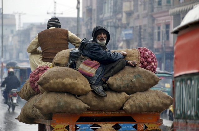 A man sits on sacks of onions loaded on a horse cart in the rain in Peshawar, Pakistan, January 4, 2016. (Photo by Khuram Parvez/Reuters)