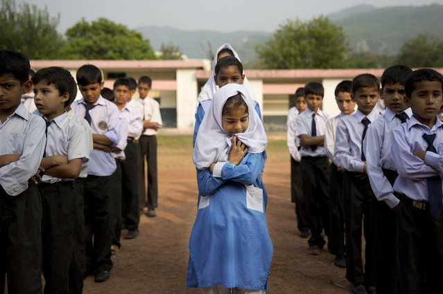 In this October 11, 2013, file photo, a Pakistani girl lines up among boys for their morning assembly where they sing the national anthem at a school in Islamabad, Pakistan. (Photo by Anja Niedringhaus/AP Photo)