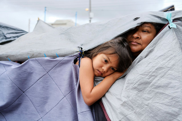 Honduran migrants Kami, 5, and her aunt Mariana listen as other migrants discuss hygiene norms within the migrant camp, at a makeshift camp at the El Chaparral border port of entry with the U.S., in Tijuana, Mexico on April 22, 2021. (Photo by Toya Sarno Jordan/Reuters)