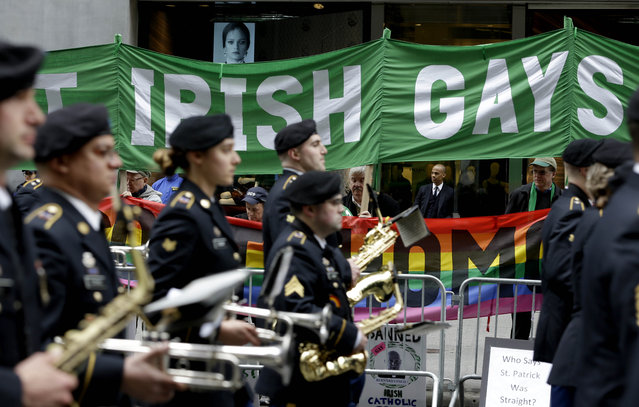 Marchers walk past a group of protesters during the St. Patrick's Day Parade in New York, Tuesday, March 17, 2015. The group was protesting the exclusion of LGBT groups from the parade. (Photo by Seth Wenig/AP Photo)