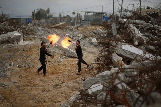 Palestinian youths blow fire as they demonstrate their ninja-style skills for a photographer in front of the ruins of buildings, that were destroyed in the 2014 war, in the northern Gaza Strip January 29, 2016. (Photo by Mohammed Salem/Reuters)