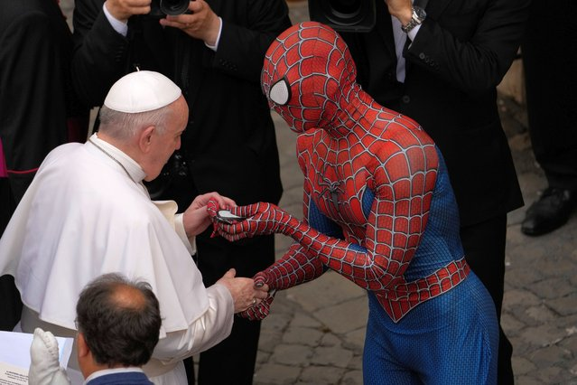 Pope Francis meets Spider-Man, who presents him with his mask, at the end of his weekly general audience with a limited number of faithful in the San Damaso Courtyard at the Vatican, Wednesday, June 23, 2021. The masked man works with sick children in hospitals. (Photo by Andrew Medichini/AP Photo)