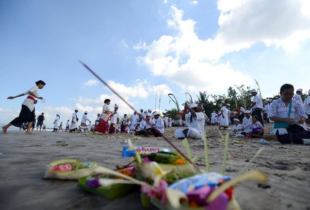 Balinese people pray during the Melasti ceremony at Kuta beach on the island of Bali on March 18, 2015. (Photo by Sonny Tumbelaka/AFP Photo)