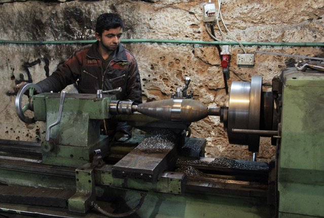 A man works on a mortar shell inside a cave used as a weapon factory operated by rebel fighters from Suqour al-Sham Brigade in Idlib countryside March 18, 2015. (Photo by Mohamad Bayoush/Reuters)