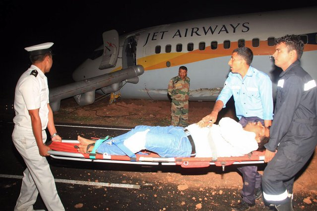 This handout photograph taken and received on December 27, 2016 from the Indian Ministry of Defence shows rescue and Indian Navy personnel moving an injured passenger away from a damaged Jet Airways Boeing 737 after it skidded off the runway following an aborted take- off at the Goa Airport in Dabolim, India' s western resort state of Goa. (Photo by AFP Photo/Indian Ministry of Defence)