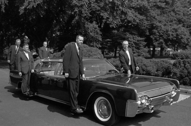 In this June 14, 1961 file photo, U.S. Secret Service agents stand on retractable stands on President John F. Kennedy's new plastic-topped Lincoln Continental limousine outside the White House, after its delivery in Washington. The car has three roof combinations, a rear seat that can be raised and lowered, retractable foot stands for Secret Service men, two two-way radio telephones, and a master control panel for power accessories. (Photo by Henry Burroughs/AP Photo)