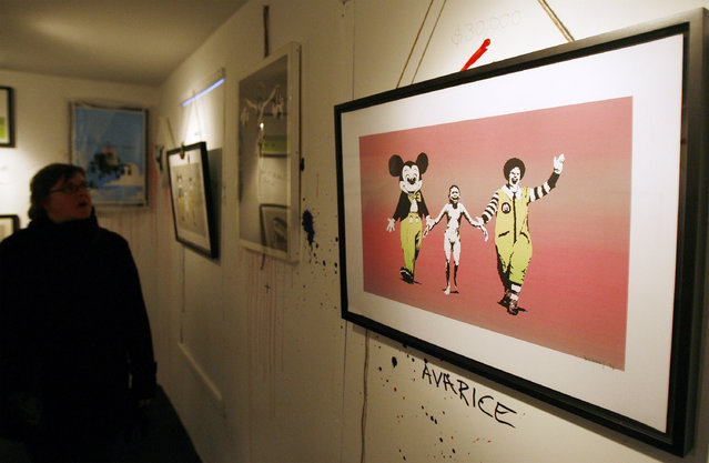 """A visitor takes a closer look at a Banksy creation entitled  """"Napalm"""" at a New York gallery in 2007. (Photo by Lucas Jackson/Reuters)"""