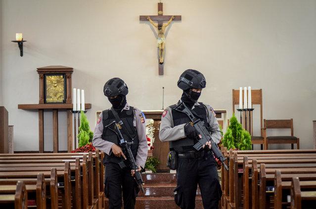 Policemen walk as they check inside Ignatius Church ahead of Christmas celebration in Cimahi, West Java province, Indonesia, December 24, 2018 in this photo taken by Antara Foto. (Photo by Raisan Al Farisi/Antara Foto via Reuters)