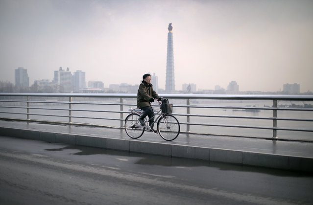 A North Korean man cycles over the Taedong river with the Juche Tower seen in the background on Wednesday, December 2, 2015, in Pyongyang, North Korea. (Photo by Wong Maye-E/AP Photo)