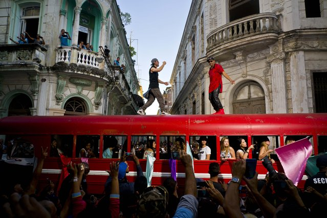 Singer Enrique Iglesias, center, and Cuban singer Descemer Bueno dance on top of a bus during the filming of their video in Old Havana, Cuba, Wednesday, January 11, 2017. Latin pop star Enrique Iglesias is in Cuba to film his latest music video for an upcoming single to be released later this year. (Photo by Ramon Espinosa/AP Photo)