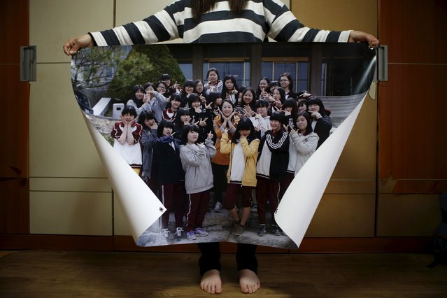 Eom Ji-yeong, mother of Park Ye-ji, a high school student who died in the Sewol ferry disaster, poses for a photograph with a picture showing her daughter (4rd L, in top line) with her schoolmates when she was 15, in her daughter's room in Ansan April 8, 2015. Her daughter's dream was to be a computer programmer. (Photo by Kim Hong-Ji/Reuters)