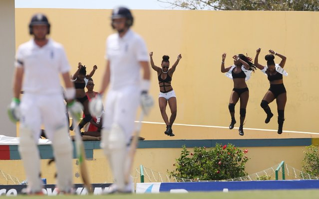 Cricket, West Indies v England, First Test; Sir Vivian Richards Stadium, Antigua, April 13, 2015: England's Joe Root and Ian Bell look on as girls dance in the background. (Photo by Jason O'Brien/Reuters)