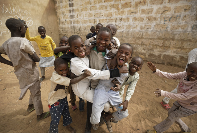 Children joke around as they play football in the sandy courtyard of Badawa Girls School, which would have been used as a polling station, in Kano, northern Nigeria Saturday, February 16, 2019. (Photo by Ben Curtis/AP Photo)