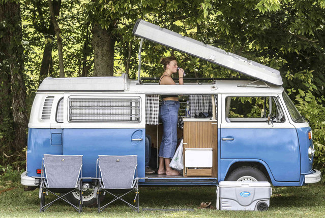 Kristina Canary takes a sip of water while catching some shade in a 1973 Vanagon she and her fiance drove to enjoy the music at the 18th annual ROMP Fest, Wednesday, September 15, 2021, in Owensboro, Ky.(Photo by Greg Eans/The Messenger-Inquirer via AP Photo)