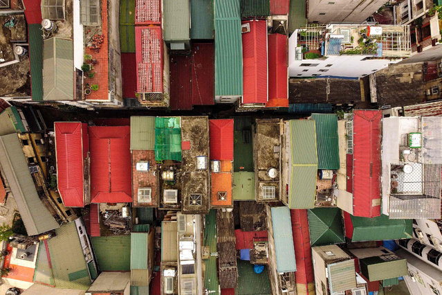 """This aerial photograph taken on June 8, 2021 shows narrow residential houses, known as """"nha ong"""" in Vietnamese or """"tube houses"""", in a densely populated urban area of Hanoi. (Photo by Manan Vatsyayana/AFP Photo)"""