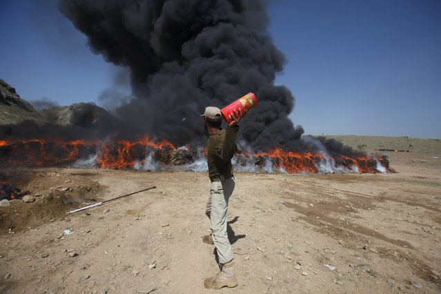 A paramilitary soldier throws a liquor bottle near a burning pile of confiscated narcotics in Shahkas area of Pakistan's Khyber Agency April 23, 2015. Narcotics including 72000 kg of hashish, 110 kg of heroin, 179 kg of opium and 950 bottles of liquor were burned and destroyed, according to paramilitary narcotics officials. (Photo by Fayaz Aziz/Reuters)