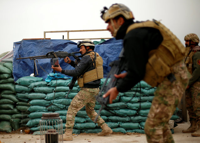 A member of the Iraqi rapid response forces fires during a battle with Islamic State militants at the Tigris river frontline near Mosul, Iraq, January 25, 2017. (Photo by Ahmed Jadallah/Reuters)