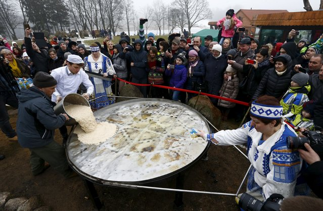 Employees pour the dough into a huge frying pan for frying dranik, a potato pancake that is the national dish of Belarus, in the Sula History Park near the village of Sula, Belarus March 7, 2016. (Photo by Vasily Fedosenko/Reuters)