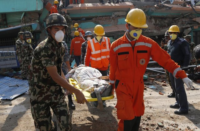 Rescue teams carry a body dug out of the collapsed Sitapyla church in Kathmandu, Nepal, Monday, April 27, 2015. (Photo by Wally Santana/AP Photo)