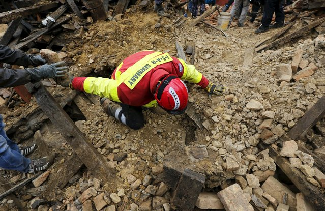 A rescuer of the German search and rescue group ISAR Germany searches for survivors of Saturday's earthquake in Kathmandu, Nepal, April 28, 2015. (Photo by Wolfgang Rattay/Reuters)