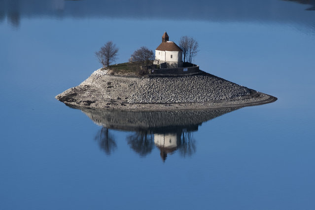 A picture taken on December 26, 2018 in Savines-le-Lac shows the Saint-Michel Chapel on a small island in the middle of the Serre-Ponçon artificial lake, one of the largest in Europe. The construction of the dam at Serre-Poncon lake started in 1955 and was completed in June 1960. (Photo by Joel Saget/AFP Photo)