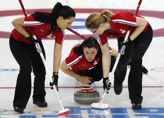Switzerland's Carmen Kueng, center, delivers the stone to sweepers, Carmen Schaefer, left, and Janine Greiner during women's curling competition against the United States at the 2014 Winter Olympics, Monday, February 10, 2014, in Sochi, Russia. (Photo by Robert F. Bukaty/AP Photo)